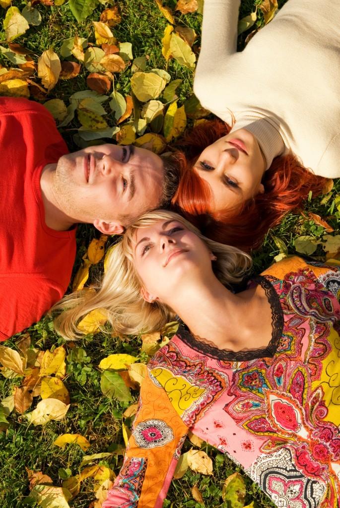 Three friends lying on autumn leaves