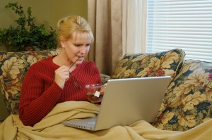 Woman working on laptop at home on the couch.