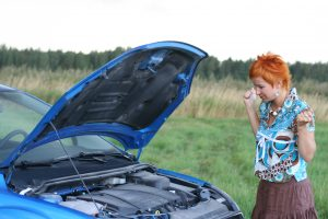 young red-haired woman with her broken car.